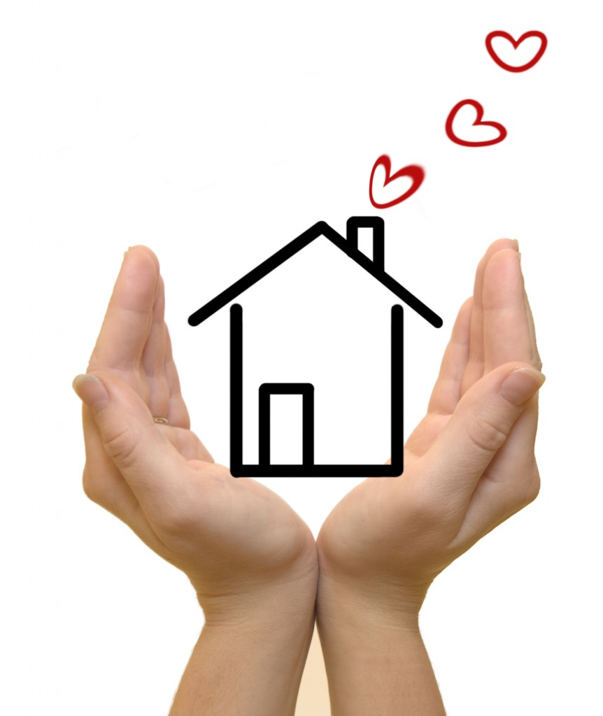 Hands protecting drawn house, hearts coming out of chimney